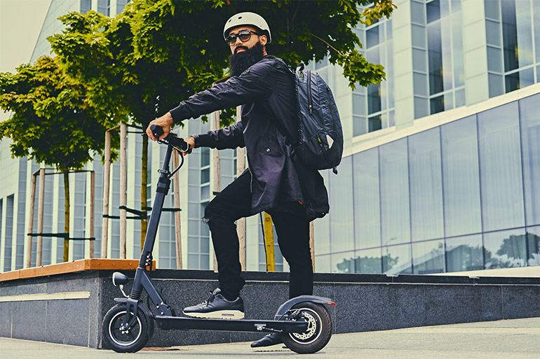 A person stands on a scooter.
