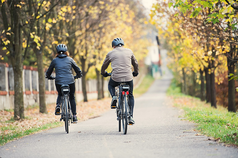 Two people ride bikes on a path.