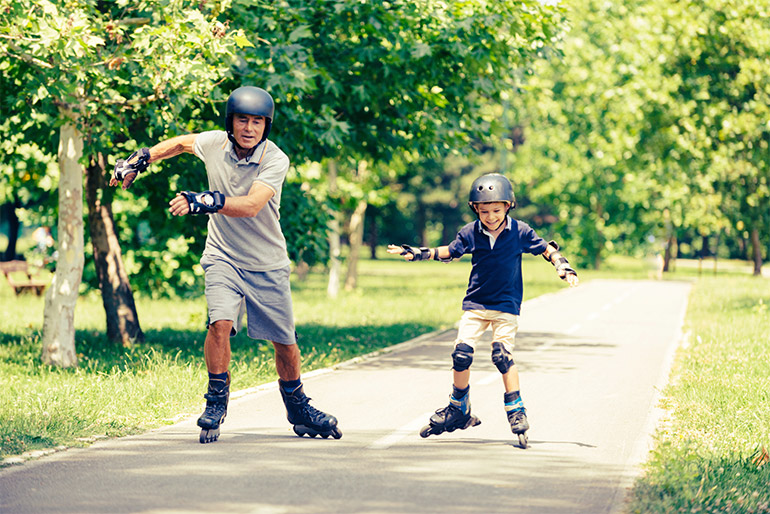 Two people rollerblade on a path.