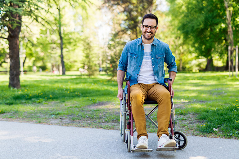 A person sits in a wheelchair on a path.